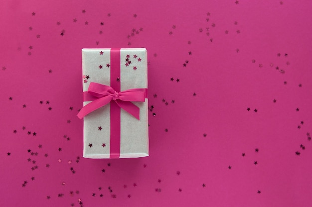 Giftbox with pink ribbon and confetti decorations on pastel paper colorful background. flat lay, top view, copy space