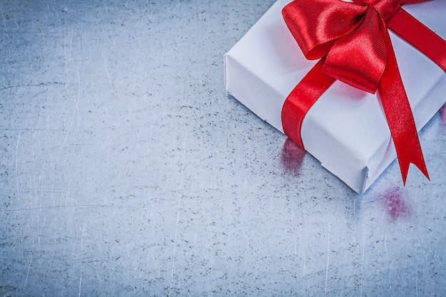 Giftbox with red bow on metallic background