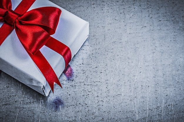 Giftbox with red ribbon on metallic background