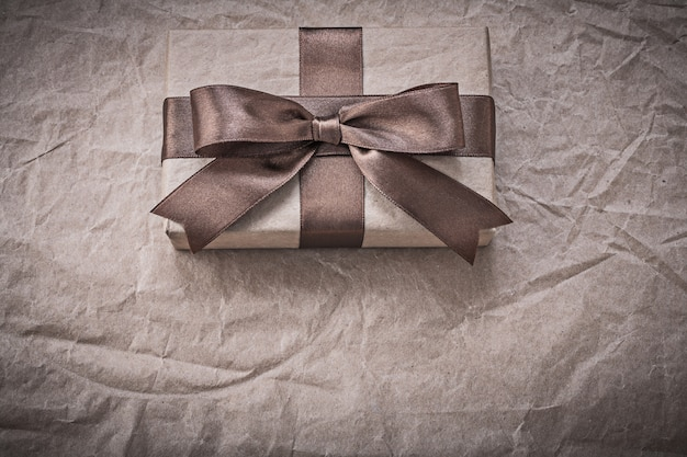 Giftbox with tied bow on wrapping paper