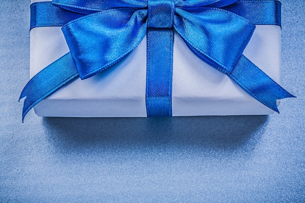 Giftbox with tied ribbon on blue color,