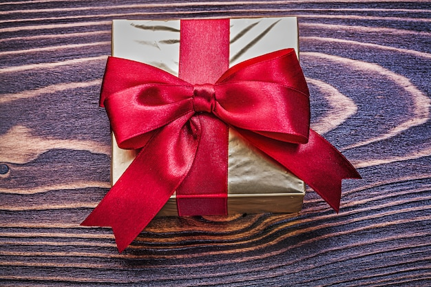 Giftbox wrapped in glittery paper on wooden board