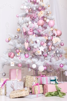 Giftboxes, pink and white christmas decorations balls hanging on a decorative white christmas tree.