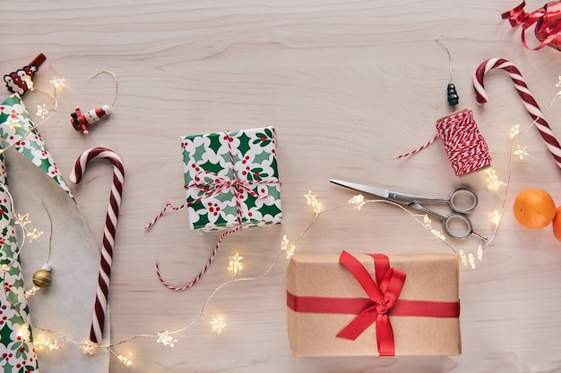 Giftboxes, 종이와 리본, 조명, 나무 배경에 사탕 지팡이 포장 선물. holdiay diy 수제 가정 장식