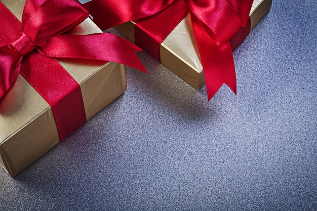 Giftboxes with red knots on grey surface