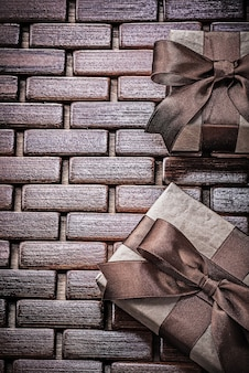 木製マットの休日のコンセプトに茶色のリボンで包まれたギフトボックス
