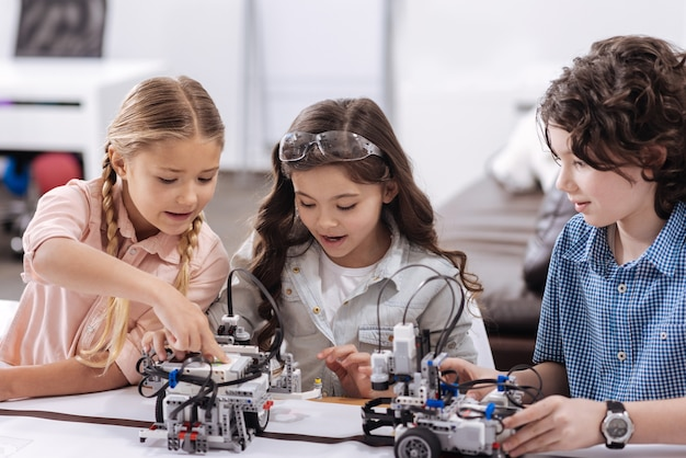 Gifted generation working together. involved initiative positive kids sitting at class and repairing robot while working on the project