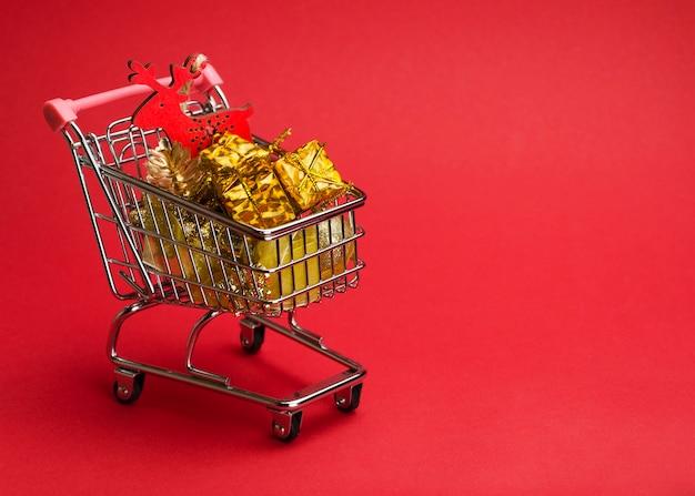 Подарки и елочные игрушки в тележке на красном