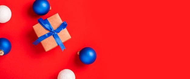赤い背景の上の贈り物やおもちゃ。上面図、フラットレイ。バナー。