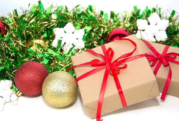 선물은 흰색 바탕에 크리스마스 장식 옆에 배치됩니다. 빨간 리본이 달린 두 개의 선물 상자입니다.