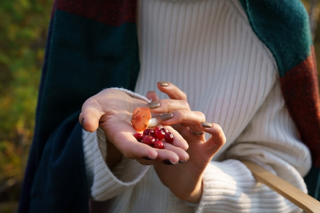 Gifts of autumn cranberries and mushroom on female hand leisure activity of walking in fall forest