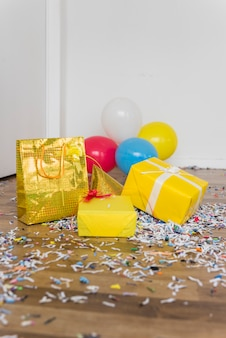 Gifts; balloons and party hat with confetti on hardwood floor