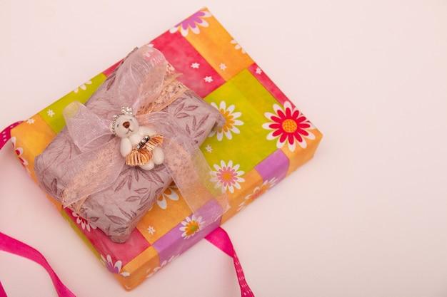 Коробка подарков в яркой упаковке на белом фоне копия пространства вид сверху розовая лента в горошек, процесс упаковки подарка, день благодарения, праздник, день рождения, подарок девушке, ребенку, подарок
