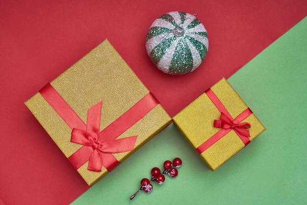 ギフトボックス、緑と赤の紙の背景にクリスマスの装飾。トレンディな写真。新年、クリスマスコンセプトコピースペース