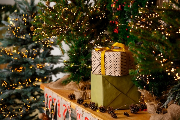 Gifts in boxes in craft packaging stand near new year tree on wooden table