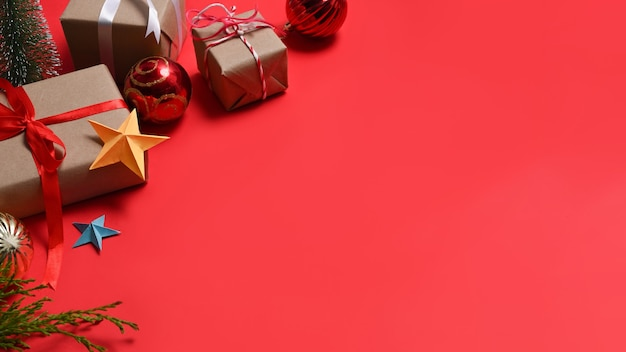 Gifts boxes and fir tree branches on red background. christmas and new year concept.