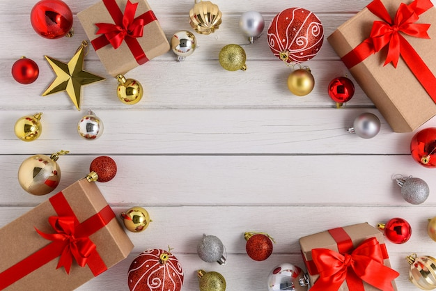 Gifts boxes with festive ribbons and christmas ornament on white wooden background