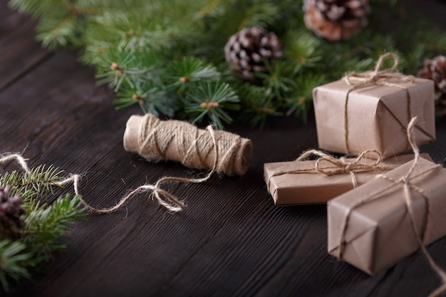 Gifts brown with a string and a roll of string and pine leaves background