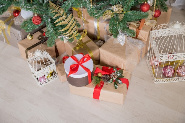 Gifts under christmas tree, winter holiday .gift boxes wrapped in craft paper with satin red ribbon bow for christmas present box.