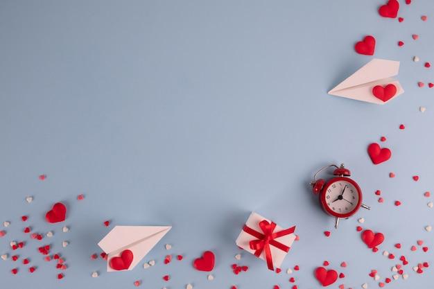 ギフト、紙吹雪、紙飛行機、パステルブルーのテーブルに目覚まし時計