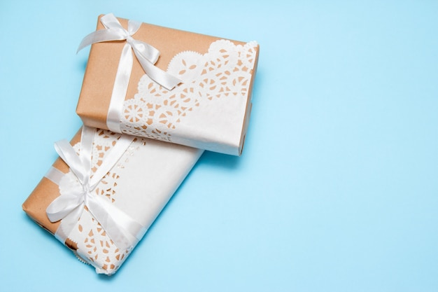 Gifts of craft paper on a blue background with copy space.