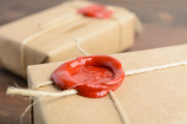 Gifts in craft paper with sealing wax over brown wooden table