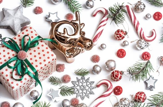 Подарки, ветки ели, красные украшения на белом фоне.