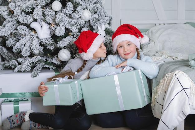 クリスマスへの贈り物。手に箱を持った赤い帽子をかぶった2人の女の子が、服を着た新年の木の背景に座っています。