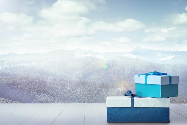 家族や友人への贈り物や背景の山々の風景。雪山と曇り空の前にある箱と香水。冬の日、休日、旅行、正月、クリスマスの時期。 。