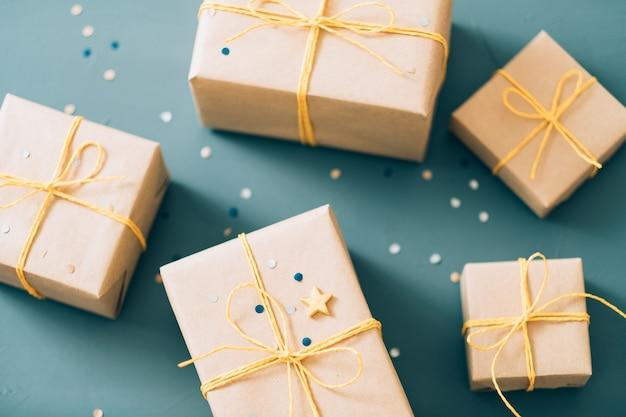 친구와 가족을위한 선물. 수제 종이 포장에 선물의 구색과 노란색 꼬기로 묶여 있습니다.