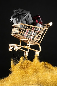 Gifts in golden shopping cart with golden glitter
