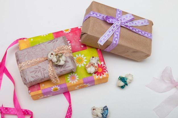 Подарки в коробках на белом фоне разместить копию вид сверху золотая лента с бантом, завернутая в оберточную бумагу, фиолетовая ленточка тесьма милые мишки для украшения яркие красочные