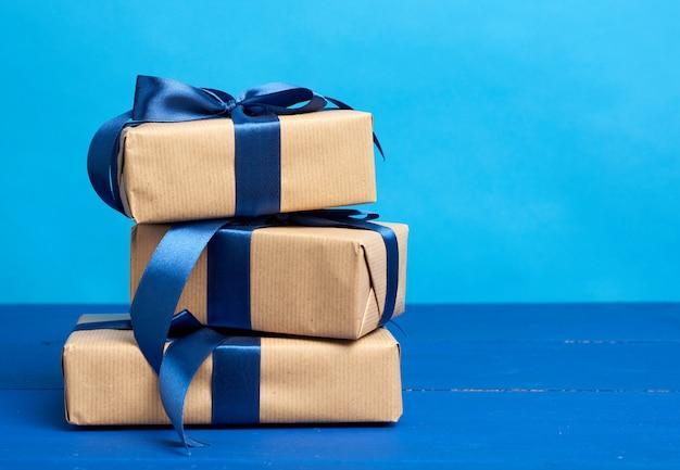 茶色のクラフト紙で包まれ、シルクのリボンで結ばれたボックスのギフト