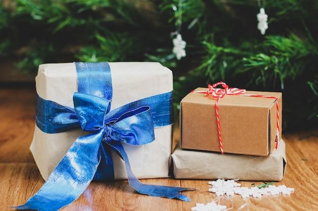 Подарки в крафтовой бумаге на фоне елки. рождественский подарок. зимняя композиция. белые снежинки. новый год. подарки крупным планом