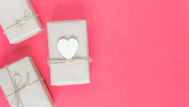 Подарки в экологически чистой крафтовой упаковке к празднику на розовом фоне.