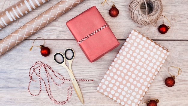 Подарки в обертываниях вокруг рождественских шаров, ниток и ножниц