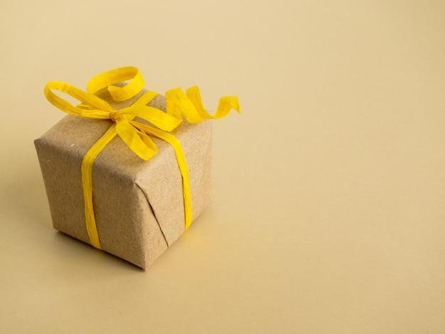 Подарки в желтом стиле на желтой поверхности. подарки упакованы в крафт-бумагу