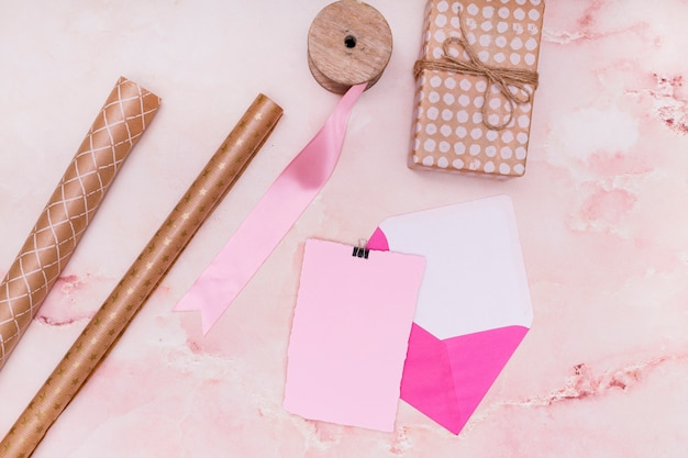 Gifts and invitation supplies on pink marble