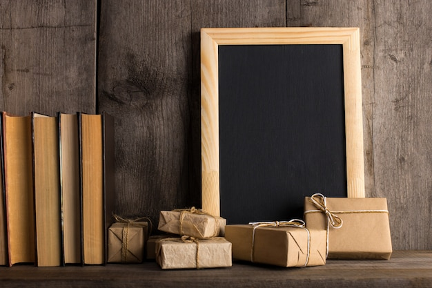 Gifts in kraft paper on an old wooden shelf and a chalk board