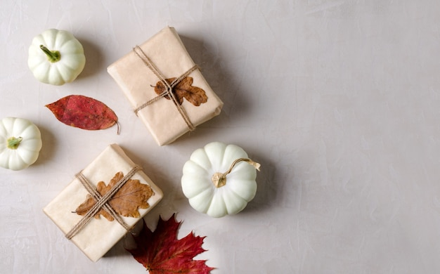Gifts in kraft paper and pumpkins on a beige background. autumn warm background