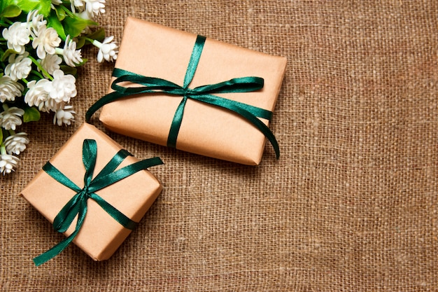 Gifts in kraft paper with white flowers laying on sackcloth.