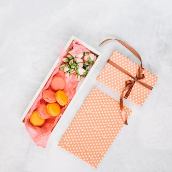 Gifts near box with macaroons and flowers