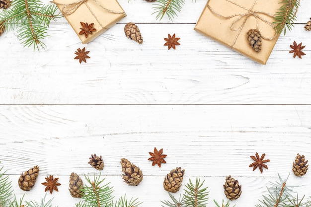 Gifts for new year wrapped in craft paper near spruce branches and cones on white wooden background top view copyspace