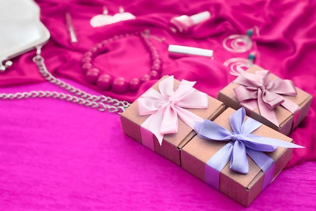 Gifts packed in kraft boxes tied with satin ribbon.