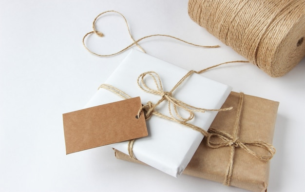 Gifts packed in kraft paper and white paper lie on a white table top view tag for copy space