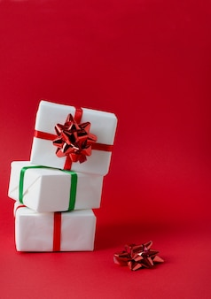 Gifts packed in white paper stand on top of each other, tied with red and green ribbons on a bright red vertical background with copy space