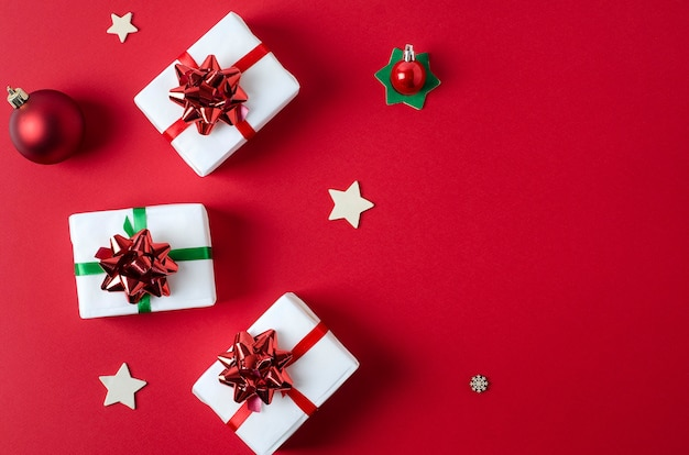 Gifts packed in white paper tied with red and green ribbons lie on a bright red vertical background with copy space