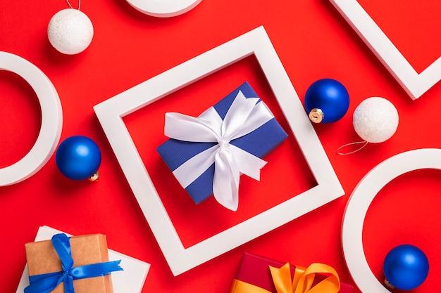 Подарки, подиум и елочные игрушки на красном фоне. вид сверху, плоская планировка.