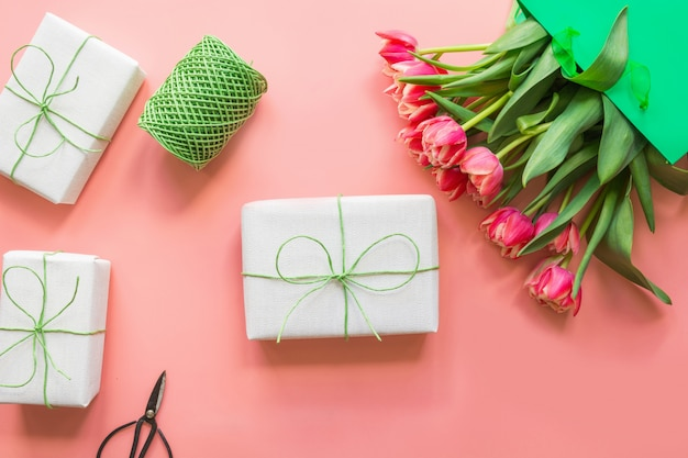 Gifts and red tulip flowers in green paper bag on pink. spring. mother day.