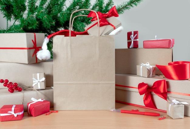 Подарки, хозяйственная сумка, новогодняя елка и упаковочные коробки на столе